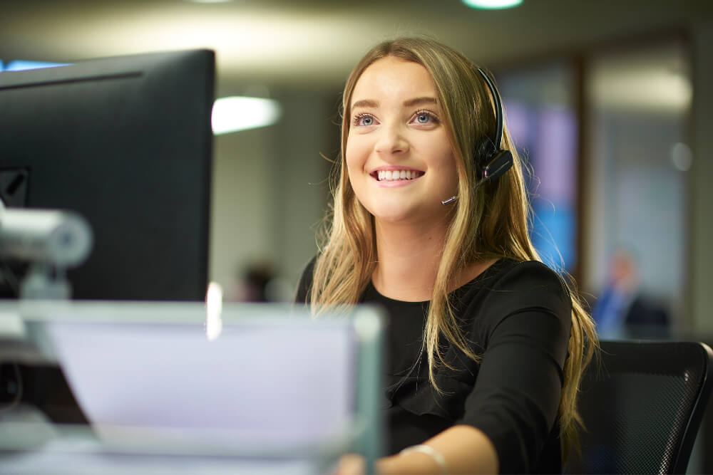 Proactive Recruitment - Image of candidate at computer smiling